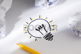 Bright Idea Concept. Hand Drawn Light Bulb On Paper and crumpled paper around. Creative process concept