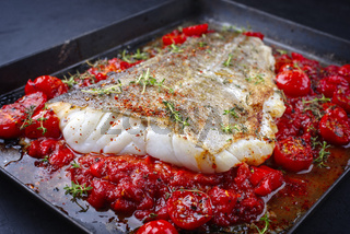 Traditional skinned backed skrei cod fish filet with tomato salsa ragu and herbs served as close-up on a rustic metal sheet