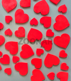 Red heart hanging on brick wall. Textured symbol of love