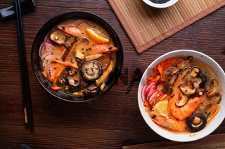 miso soup with mussels, shrimps , shiitake mushrooms and vegatables. served in black&white  bowls at dark brown wooden table. flat lay