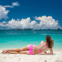 Woman wearing pink bikini laying on beach