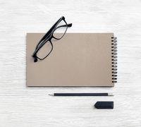Kraft notebook, glasses, pencil, eraser