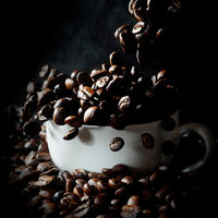 Falling coffee beans in white cup