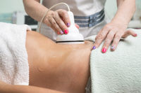 Woman getting ultrasound cavitation treatment by cosmetologist. female client enjoying anti-cellulite procedure at beauty salon.