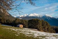 Barn on a sunny alpine winter meadow with melting snow, Wildermieming, Tirol, Austria