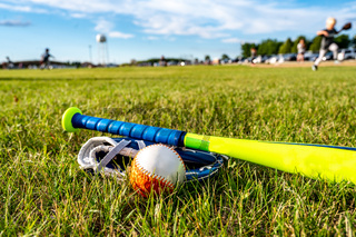 Tee ball, glove, and bat on green grass. Equipment commonly used in youth sports.