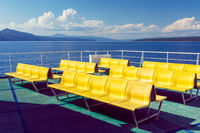 Empty yellow chairs - benches - on the upper deck of the Adriatic ferry