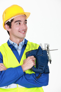 Smiling worker with an electric jigsaw