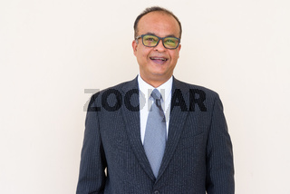 Portrait of Indian businessman smiling against plain wall outdoors
