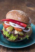 Cheeseburger auf blauem Teller mit Chili