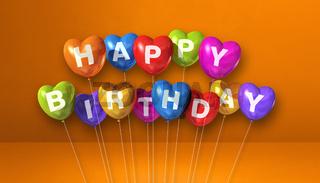 Colorful happy birthday heart shape air balloons on orange background scene. Horizontal Banner