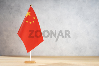 China table flag on white textured wall. Copy space for text, designs or drawings