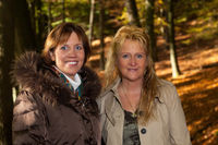 Two pretty and merry women in the autumn forest