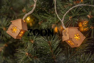 Winter time background. Christmas tree garland in the form of small houses on a fir tree .