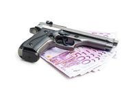 Hand gun and euro banknotes.
