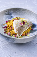 Modern style traditional sauteed skrei cod fish filet with skin in a bed of Persian jeweled saffron rice pilaw served in ceramic design bowl as close-up