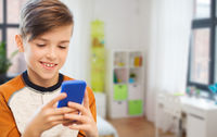 boy with smartphone texting or playing at home