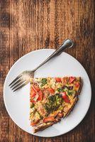 Slice of vegetable frittata on white plate