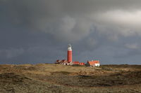 the red lighthouse and houses on Texel island, Holland