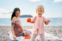 Little girl with a mold in her hand stands on a pebble beach against the background of a smiling mother