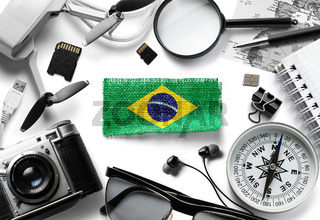 Flag of Brazil and travel accessories on a white background.