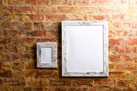 Composition of white cards in frames with copy space and decorations on brick wall