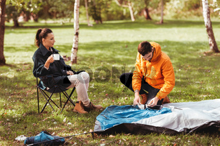happy couple setting up tent outdoors