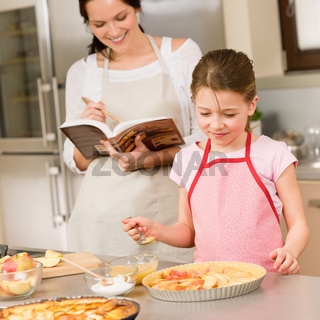 Mother and daughter make apple pie recipe