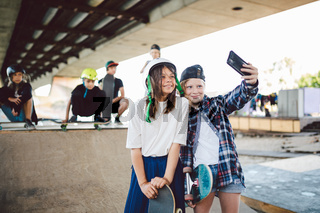 Hipster girlfriends taking selfie on ramp in the skate park. Two girls skateboarder friends taking photo portrait with mobile phone in the street skatepark. Teenagers taking self-portrait together