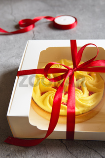 Delicious yellow tart in the gift box. Tasty and colorful dessert - lemon curd tart made by chef