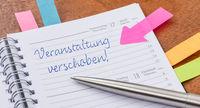 Daily planner with the entry Event postponed in german - Veranstaltung verschoben