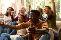 Group of happy diverse female and male friends watching tv and drinking beer together at home