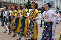 People in traditional folk costumes perform the Bulgarian folk dance