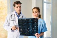 Krankenschwester und Radiologe betrachten MRT Aufnahme