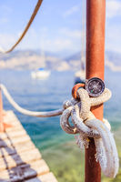 Sailing: nautical compass on a sailing rope, pier. Sailing boats in the background.