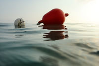 Sea surface photographed from water level, sea buoy in back. Abstract marine background.