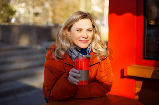 Adult woman with drink to go in street cafe