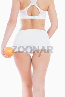Woman in sportswear holding orange