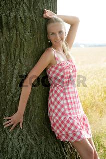 Frau lehnt an einem Baum