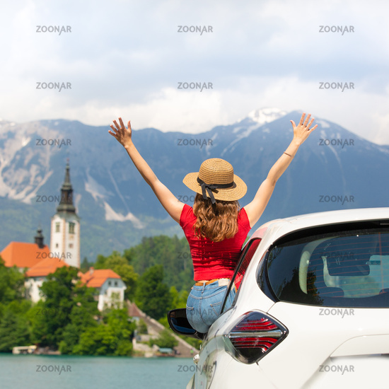 Two young female friends driving, listening to good music in car, enjoy road trip in summer.