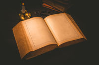 Old antique book with empty pages and candle in vintage style  on black background
