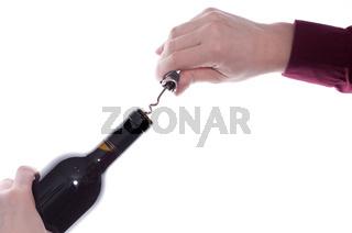 Hand dreht einen Korkenzieher in den Korken einer Weinflasche