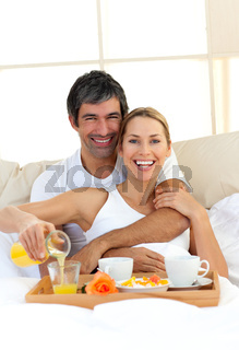 Romantic couple having breakfast lying in the bed