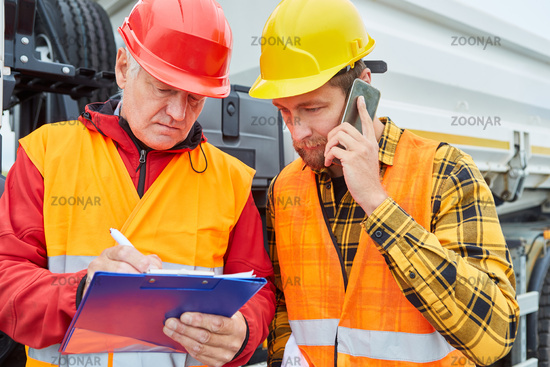 Site manager and foreman with checklist and smartphone