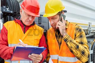 Bauleiter und Vorarbeiter mit Checkliste und Smartphone
