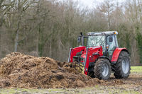Red tractor with front loader in front of a manure heap