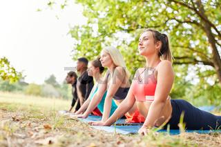 Gruppe Leute im Yoga Kurs machen Dehnübung