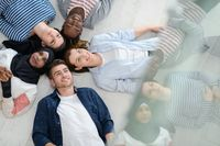 top view of a diverse group of people lying on the floor and symbolizing togetherness