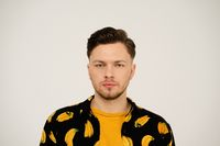 Close up serious look on face of a handsome man in dressed banana shirt and yellow t shirt under looking at camera isolated on white background