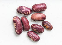 several red spotted pinto beans close up on gray